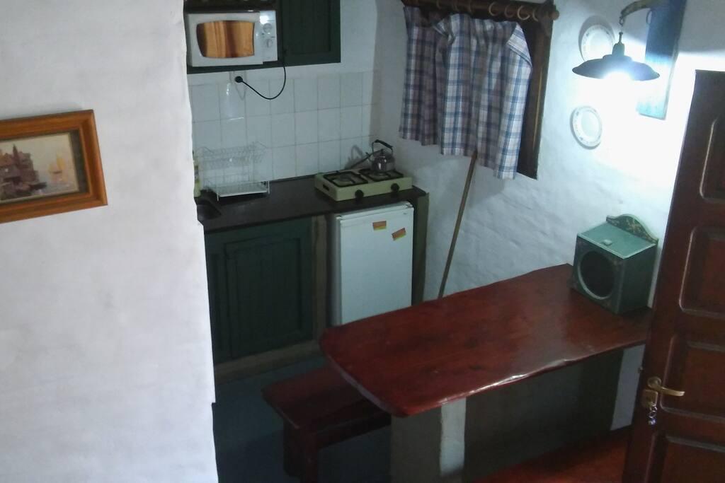 kitchenette y mesa con bancos para comer