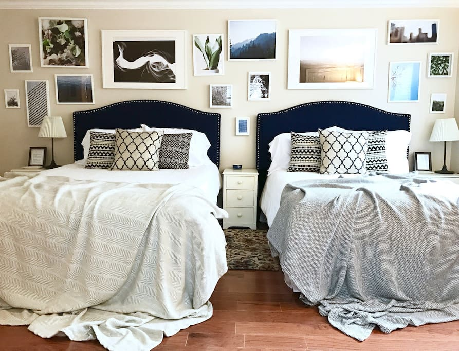 The Navy Room featuring a Queen and a Full sized bed, a private bathroom, an empty chest of drawers and a full sized closet to utilize.