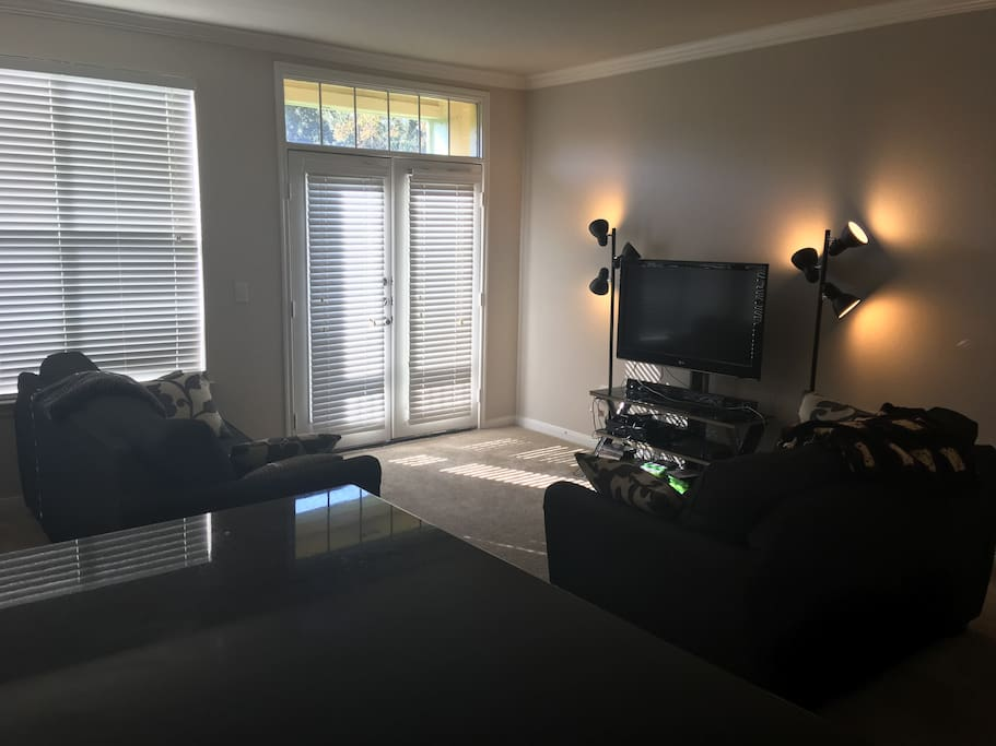 Living room with fold-out couch, love seat, foosball table, flat screen and Xbox One. Entertainment includes xbox games, blu-rays, Netflix and Amazon Firestick.