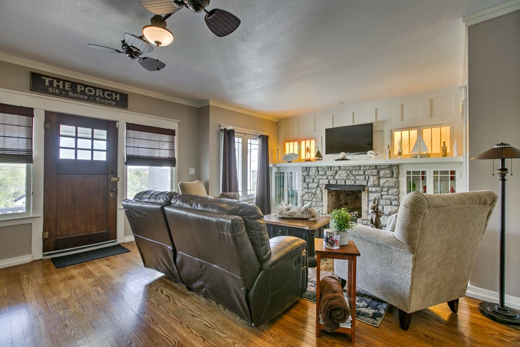 Charming living area, stone fireplace, hardwood floors, comfortable reclining leather couch