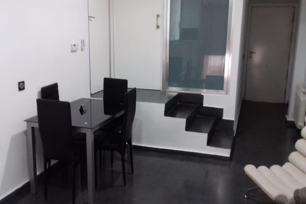 Salón zona de comedor y escaleras de acceso al dormitorio y  al baño