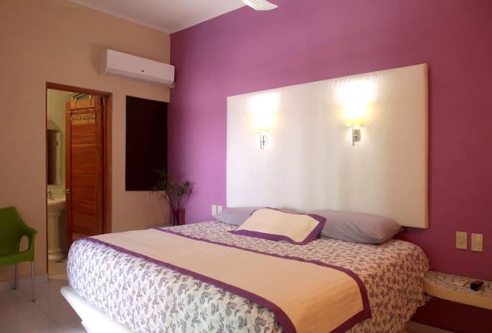Habitación con baño, caja de seguridad, TV, ventilador y aire acondicionado.