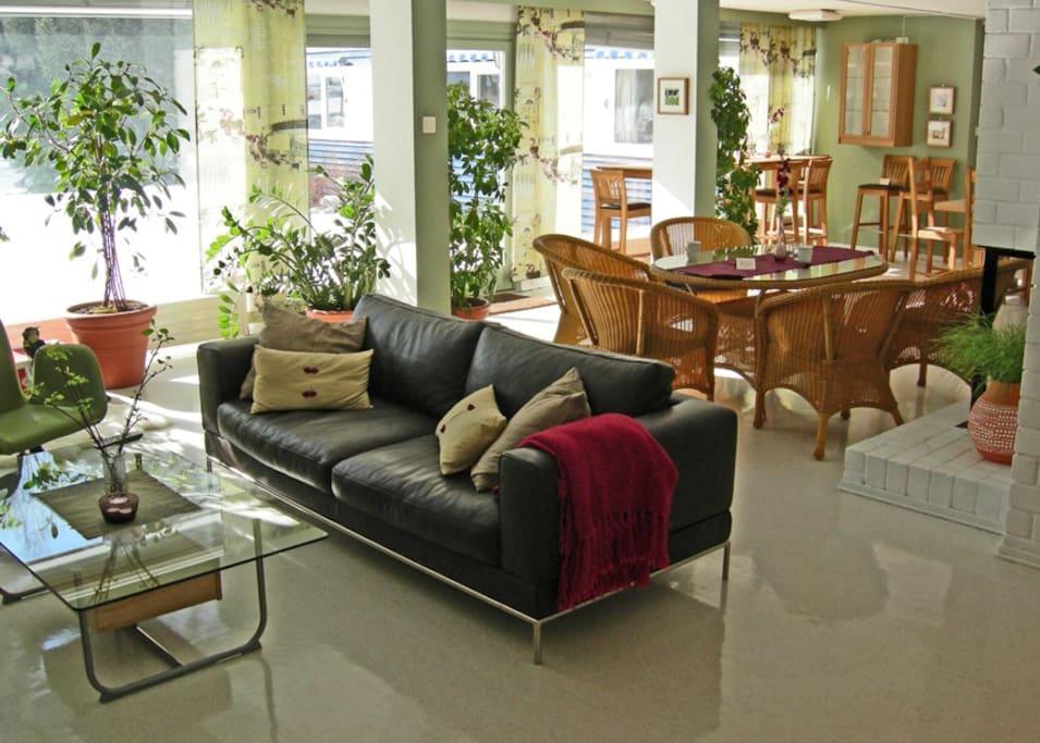 Felles oppholdsrom med sofa, sittegruppe og langbord.