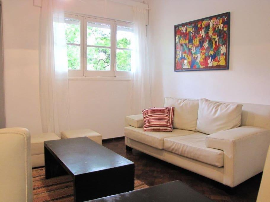 Comodo living con sofá y puffs de cuero