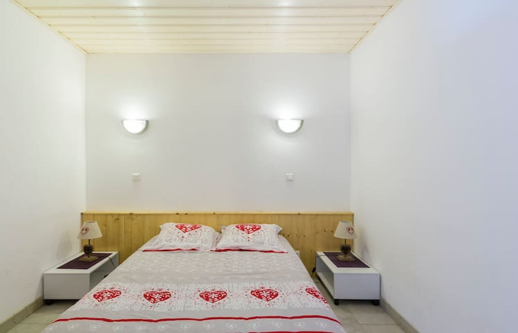 chambre 1 avec un lit de 140 cm, deux tables de nuit avec lampes de chevet et un coin bureau dressing