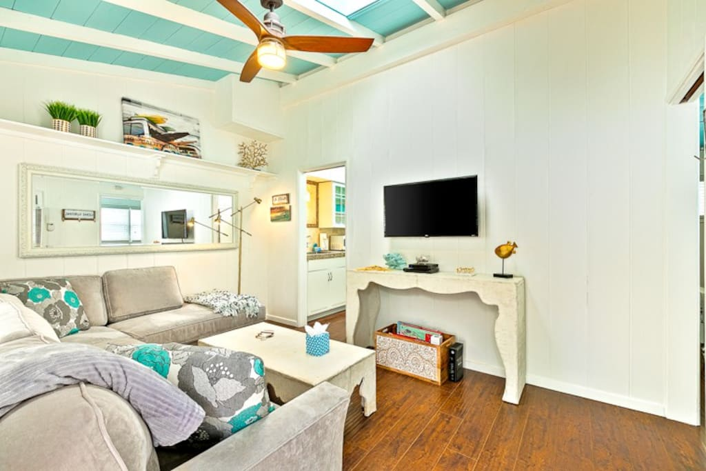 Beach inspired Living Room with hard wood floors and a ceiling fan for your comfort.