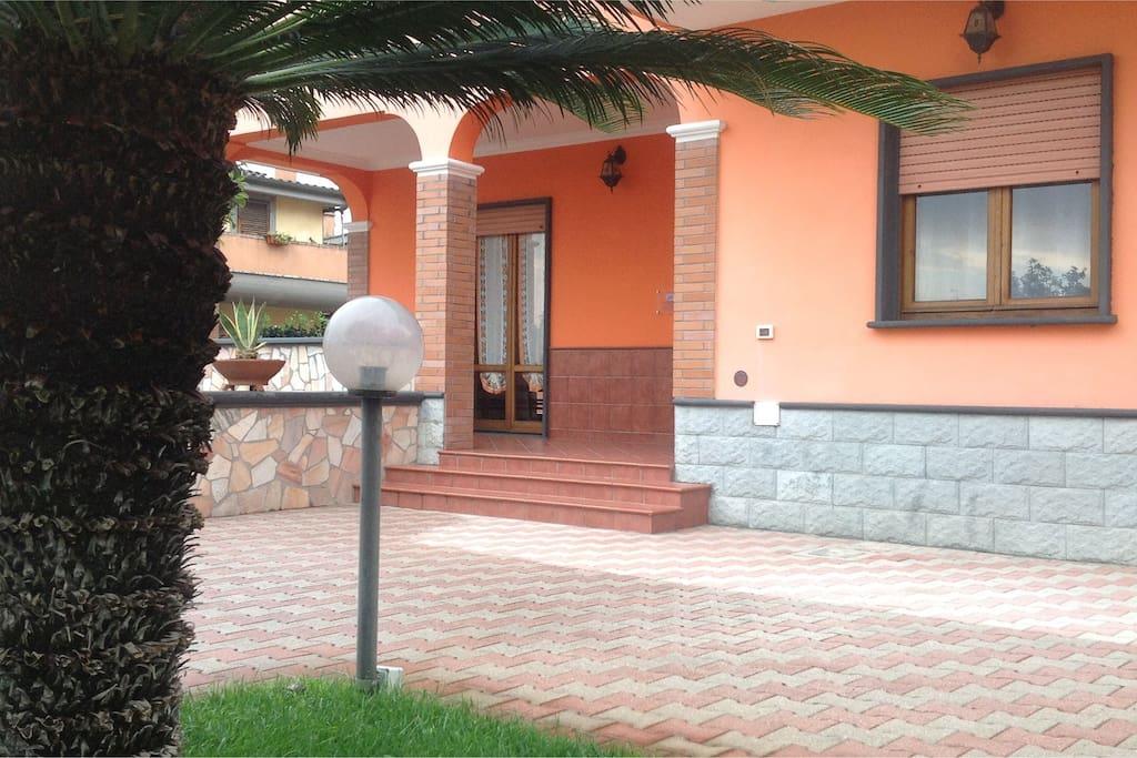 Visuale laterale della casa con vista porzione di giardino anteriore.-