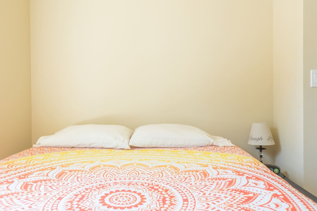 Indica Room comes with queen-sized bed, nightstand with lamp, and alarm clock with AC & USB power.
