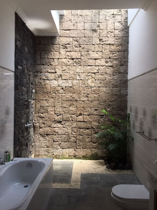 """The bathrooms feel """"outdoors"""" but are enclosed. Lovely high ceilings, plants and skylights."""