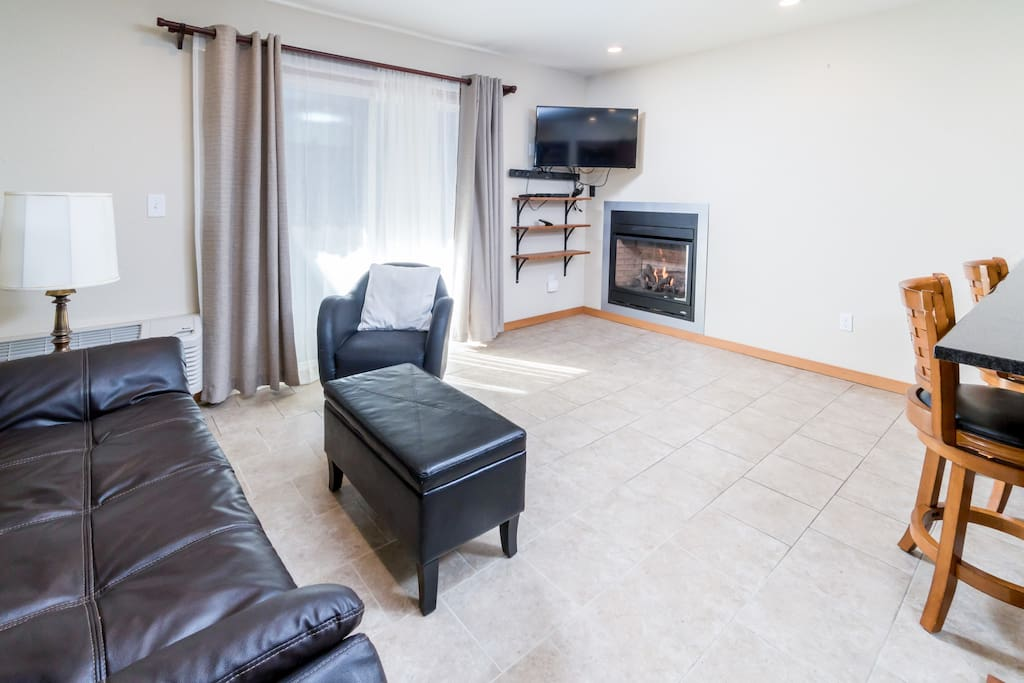 Living area with 3-seat leather sleeper sofa, warm gas fireplace, and flat screen TV.