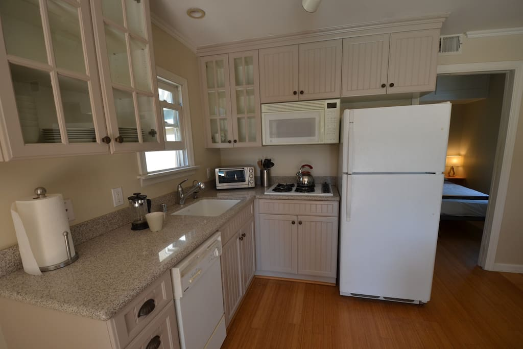 Full kitchen with refrigerator, cooktop, microwave, dishwasher & toaster oven.  Dishware, cookware and common kitchen utensils are provided (including coffee press, small blender, and tea kettle)