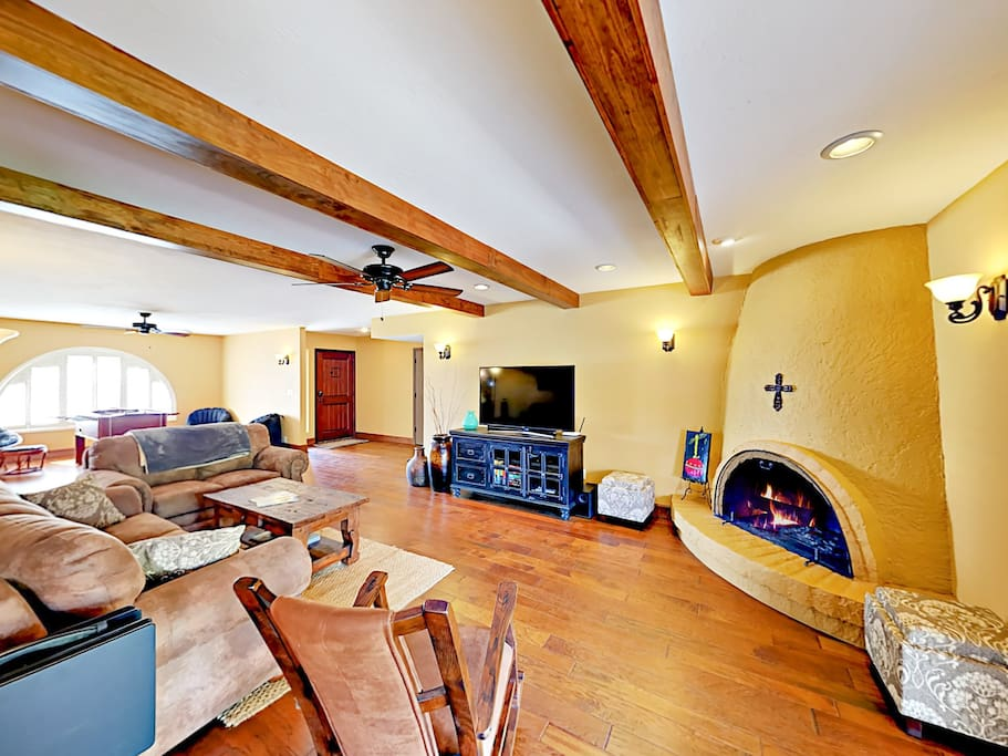 "Welcoming living room with 55"" smart TV and wood-burning fireplace."