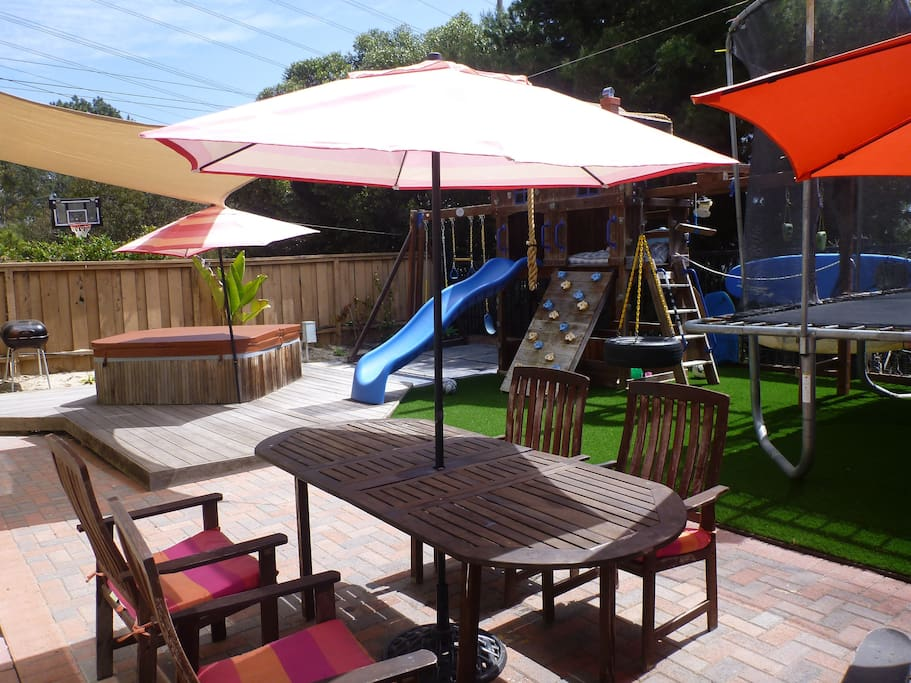Private backyard with outdoor dining, hot-tub, play house, swings and trampoline