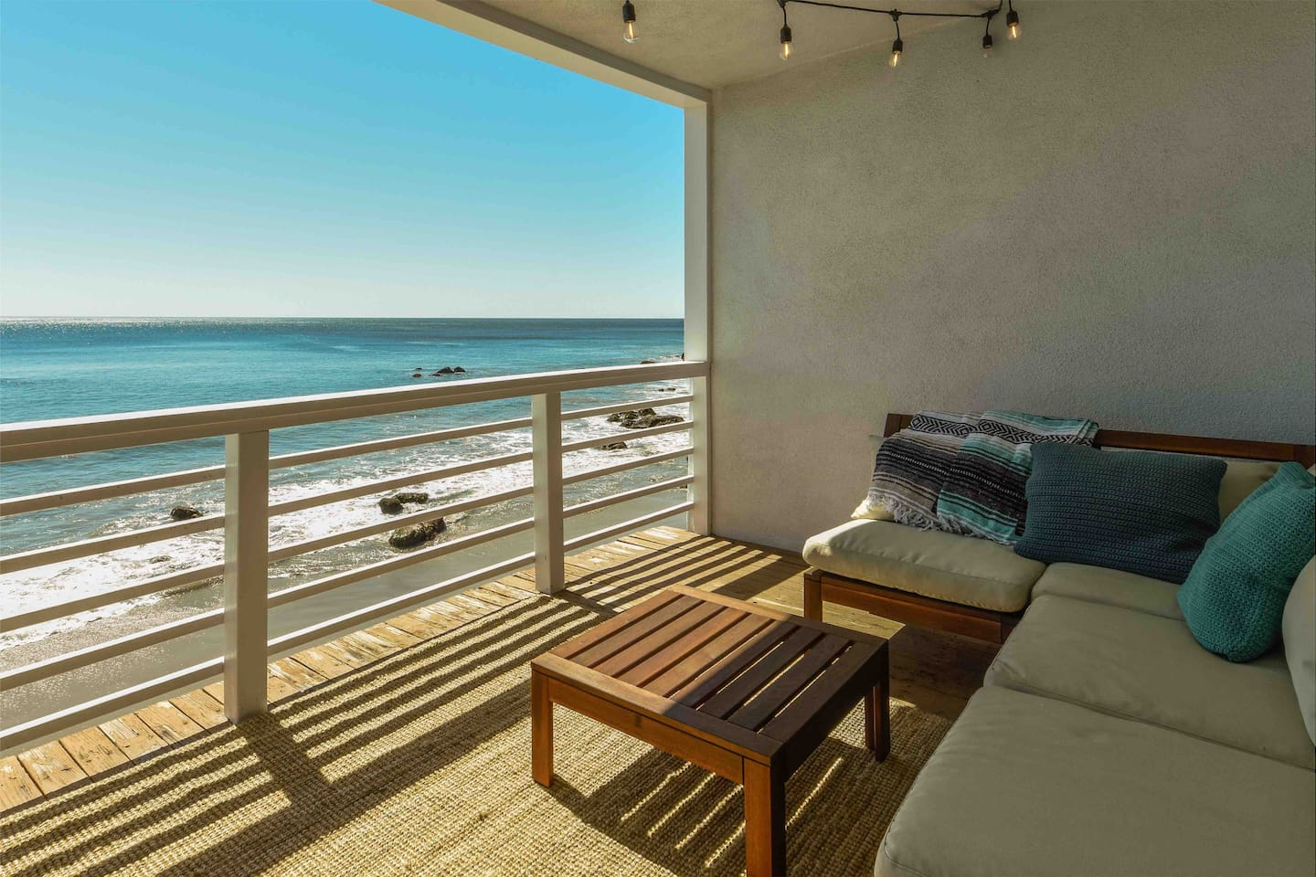 View from private patio with lounge seating and a table for 2 or 4 overlooking Malibu beach