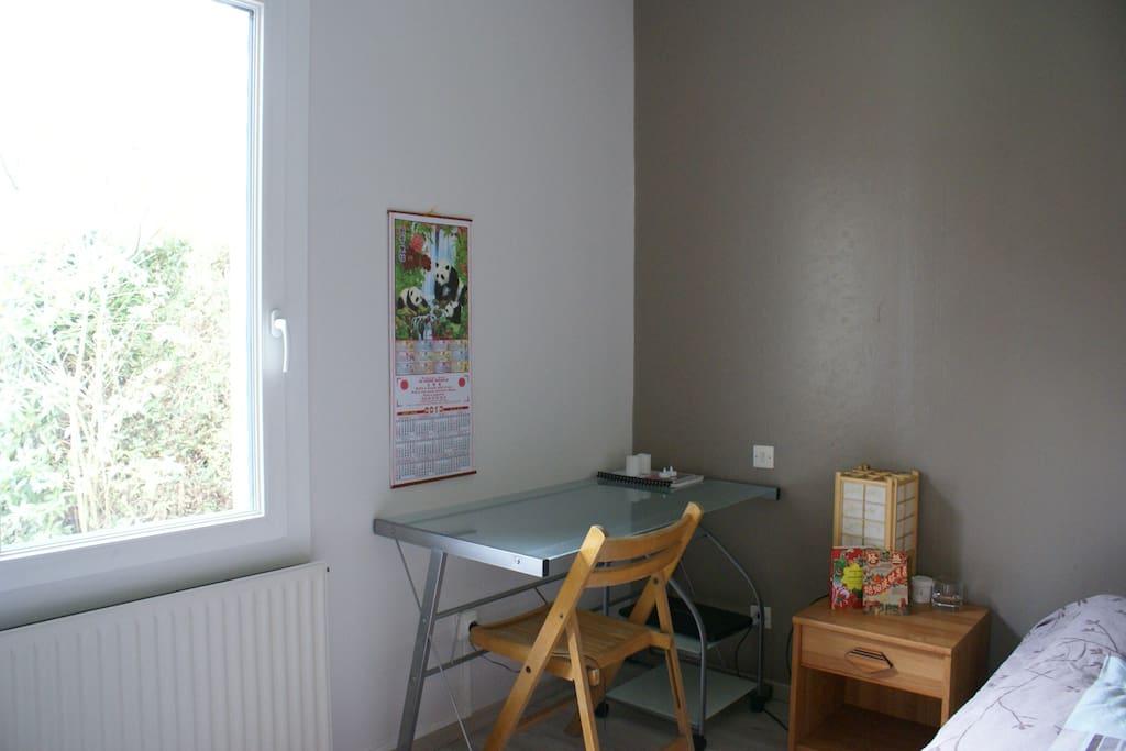 Bureau près de la fenêtre donnant sur le jardin