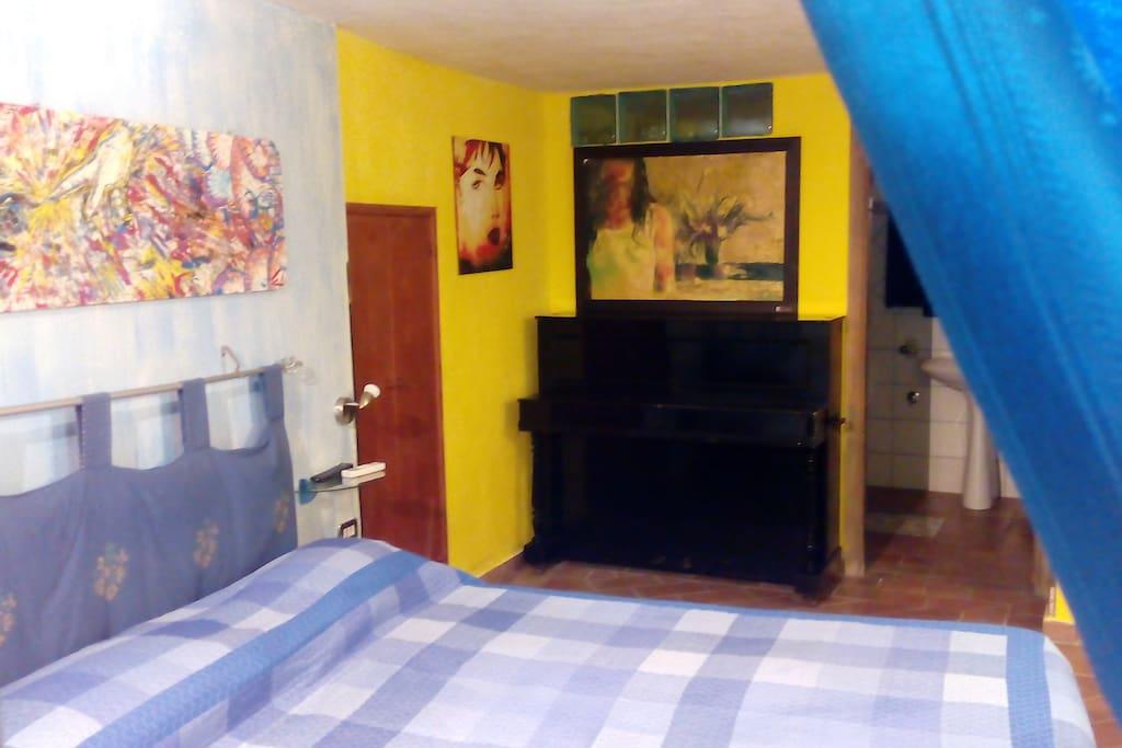 camera da letto con pianoforte  e zona bagno in camera
