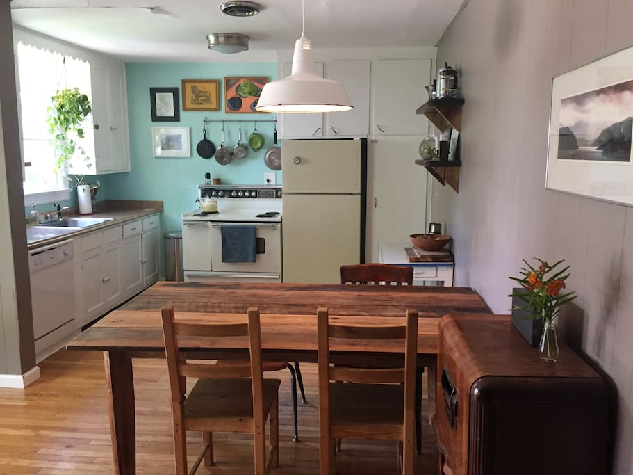 A lovely bright kitchen with wood floors and a farm table.