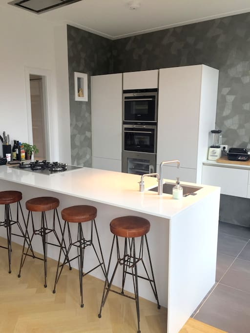 fully equipped kitchen with steam oven, oven, microwave, dishwasher
