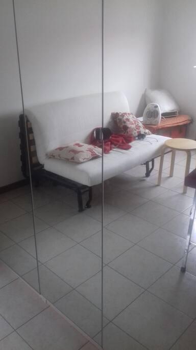 Stanza con armadio a specchio ikea che riflette divano tre posti che diventa comodo letto a due piazze