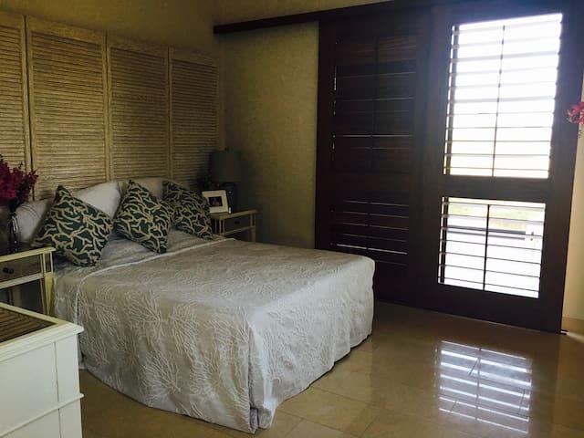 Cuarta recámara con cama queen size, balcón y vistas al campo de golf