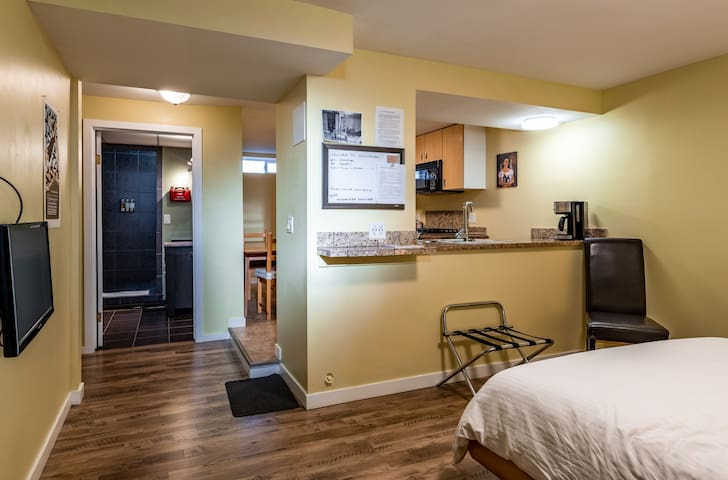 350 square foot studio suite with a large, well equipped kitchen.  View from bedroom toward bath and kitchen.