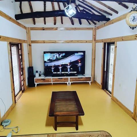 거실  겸 침실로 사용할 수 있고 넷플렉스가 설치되어 있고, 56인치 tv와 사운드 바가 있습니다  양쪽으로 트인 문을 열면 멋진 안마당과 뒷마당을 볼 수 있어요
