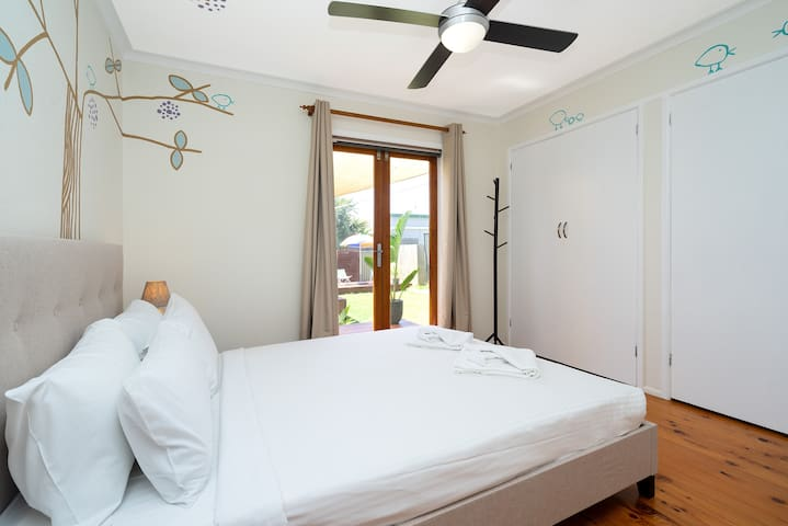 One bedroom features a queen bed dressed in hotel quality linen, in-built wardrobes and access to the garden