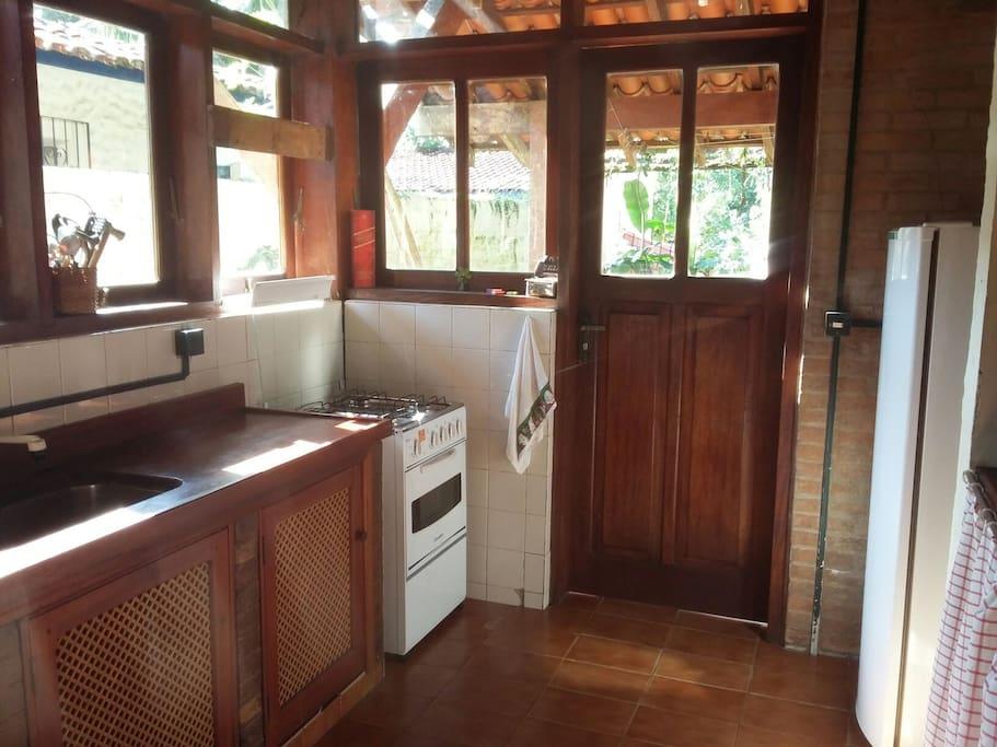 cozinha, pia c bancada em madeira e cuba de inox, micro ondas, fogào e geladeira simples.