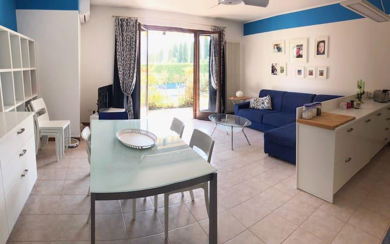 zona giorno openspace con cucina a vista, divano con penisola (divano letto matrimoniale) tavolo pranzo, tv, affaccio su terrazzo con tavolo e sedie per pranzare fuori, distanza piscina 5 metri