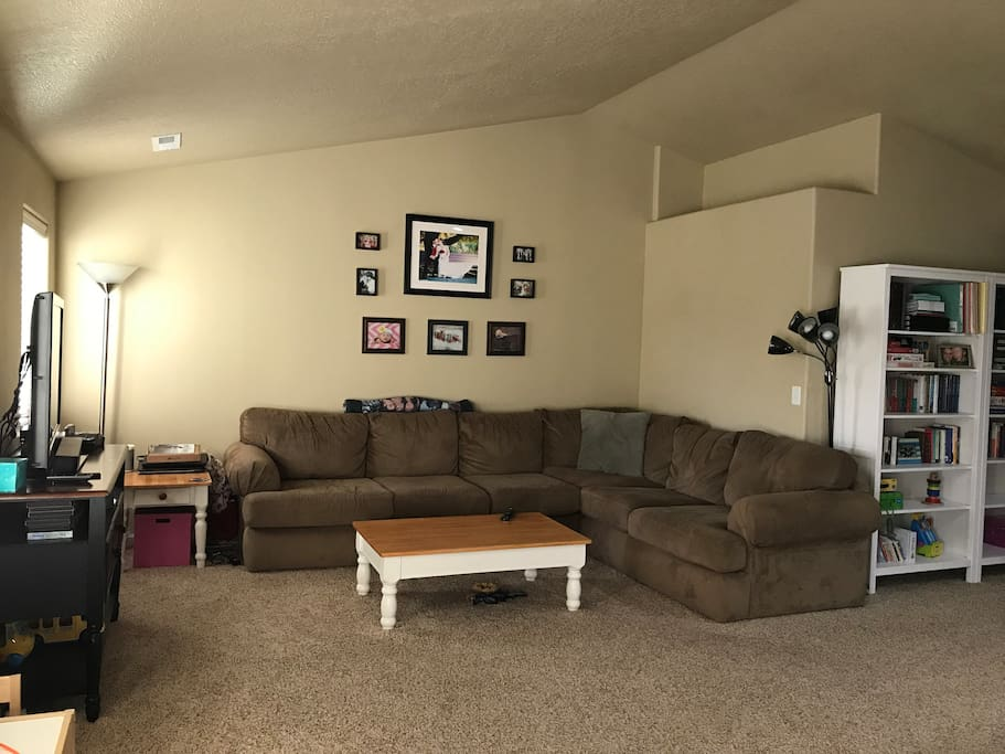 Living room with large sectional couch, TV, room for air mattress