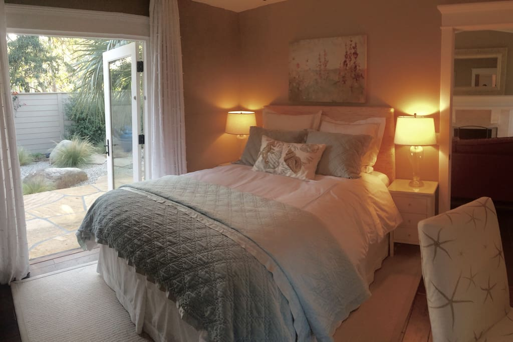 Cozy clean bedroom with very comfortable queen bed, dressing table, armoire, walk-in closet, en-suite bathroom, and French doors opening to private garden and eating area with private outdoor shower.
