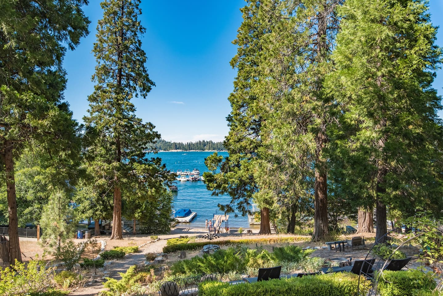 Front yard, private beach, and lake; This is the view from the dinning nook, living room, game room, main deck, second deck, and master bedroom. The trail is right in front of the house and goes to the village (left), and around the lake hiking (right).