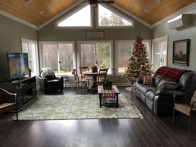 Sunroom with TV, power recliner couch, and game table