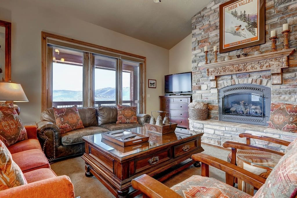 Grand living / family room with flatscreen HDTV, floor to ceiling oversized windows to allow natural light, private balcony and stone fireplace.