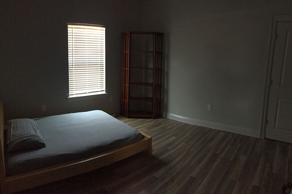 Spacious middle bedroom with platform bed and closet.