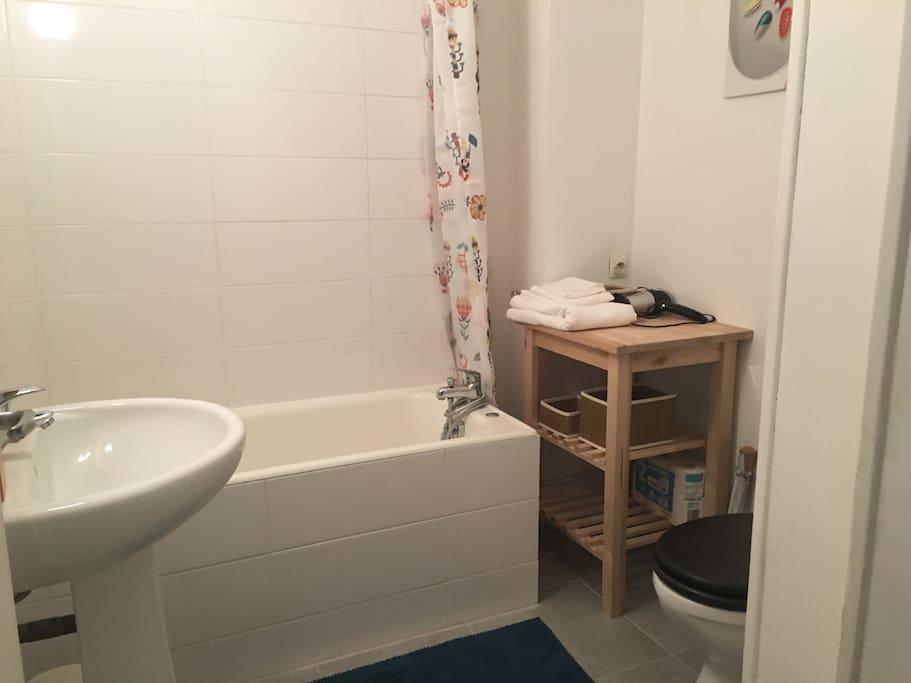 Grande salle de bains avec baignoire et toilettes.