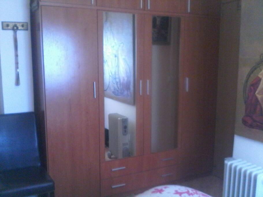 Habitación exterior privada con armario y radiador eléctrico.