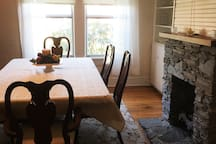 Dining room features Queen Anne style dining set and rock-fronted gas fireplace.