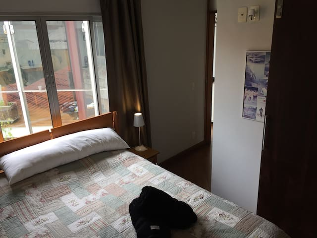 Suite privativa com janela ampla, cortina blackout e criados-mudos com abajours.