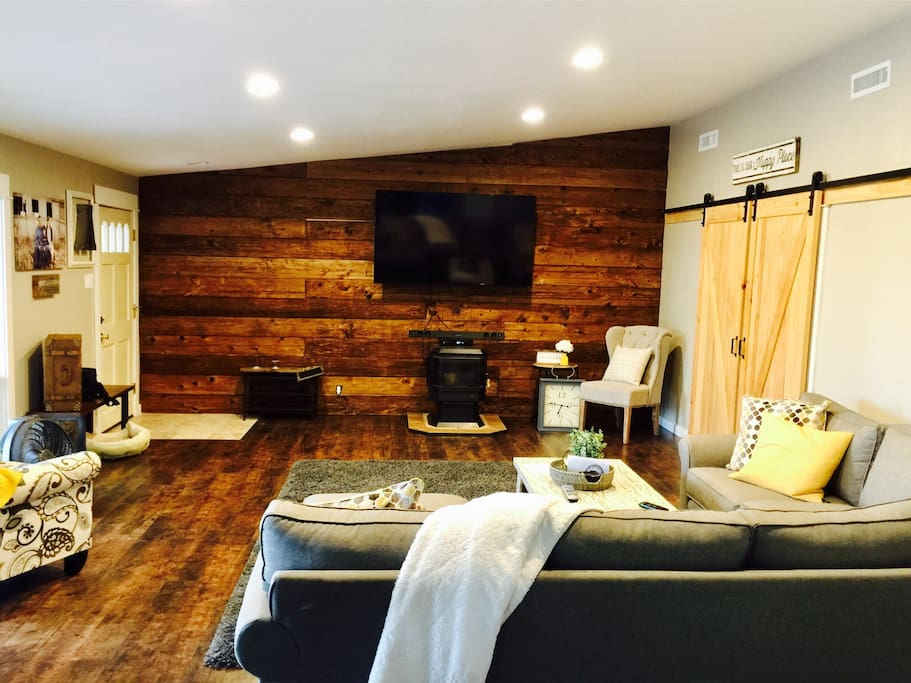 """Cozy living room with 70"""" tv and warm wood wall!"""