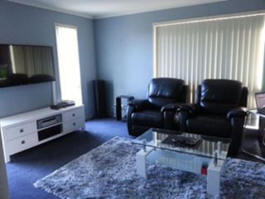 Comfortable lounge with leather couches and big screen TV