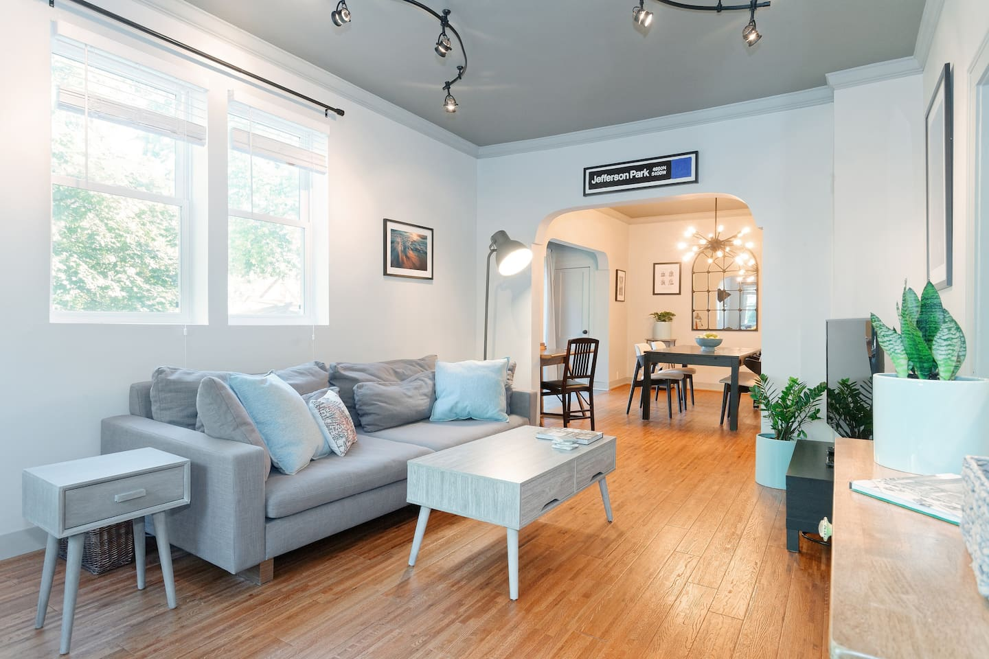 """Light flooded living room with hardwood floors, 50"""" Smart TV, and extra long & deep sofa."""