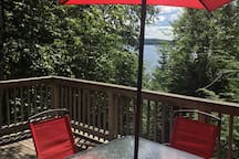 View from screened-in porch across deck to lake