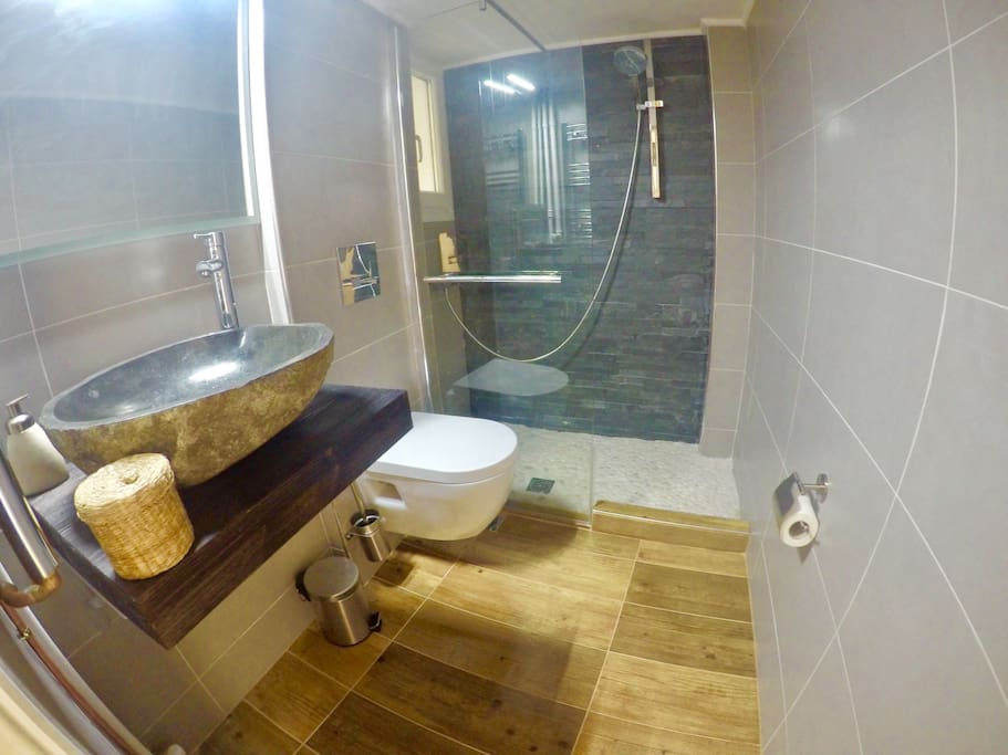Enjoy a relaxing shower in the elegant bathroom. The main elements here are wood and stones.