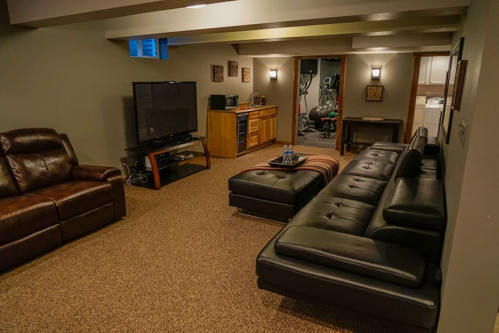 Living room features a large screen tv, wet bar & work station.