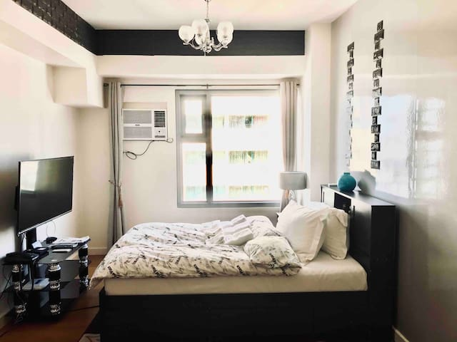 The main bedroom area with a double sized Malaysian-wood bed frame, a premium flex memory mattress for maximum comfort, a bed side table with a reading lamp and a variety of books, a 43-inch smart TV, air conditioning with remote and a chandelier.