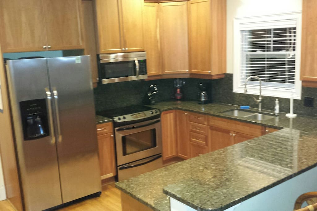 The kitchen is all stainless with a glass top stove and a large  refrigerator.