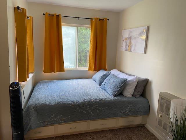 Sleeping nook features queen bed, lots of pillows, darkening curtains, and built in drawers for extra storage.
