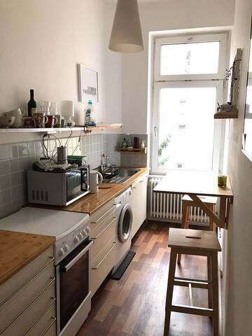 Voll ausgestattete Küche mit Sitzmöglichkeiten für 3 Personen, Waschmaschine, Herd mit Ofen, Kühlschrank und Mikrowelle