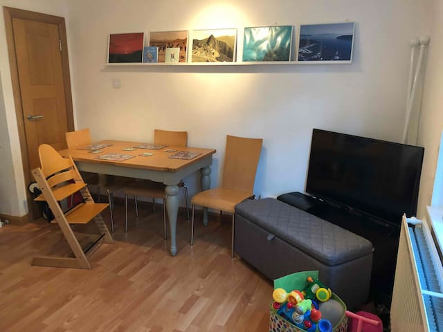 Living room with toddler chair  Baby / Toddler toys and books available including toy kitchen and ball pool.